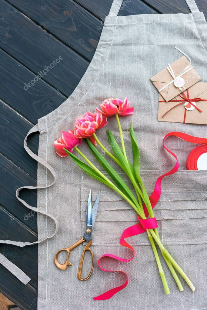 Beautiful tulip flowers with envelopes, ribbon and scissors on apron