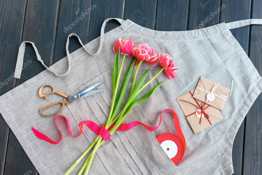 Top view of beautiful tulips with envelopes, ribbon and scissors on apron