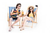 Photo couple relaxing on beach chairs with cocktails and taking selfie, isolated on white