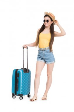 Smiling girl in sunglasses and hat posing with luggage for trip, isolated on white stock vector