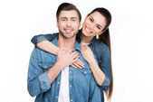 cheerful young couple hugging and looking at camera, isolated on white