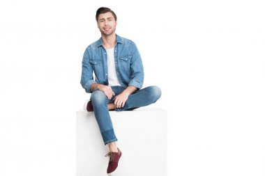 Young smiling man in jeans sitting on white cube, isolated on white stock vector