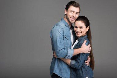 cheerful couple hugging isolated on grey
