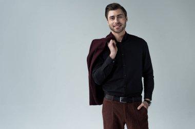 smiling stylish man posing with jacket, isolated on grey