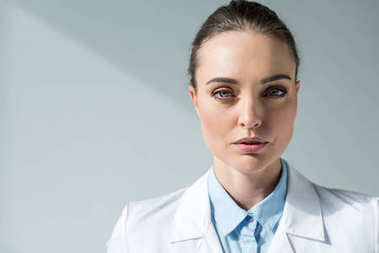 close-up portrait of serious female doctor in white coat looking at camera on grey