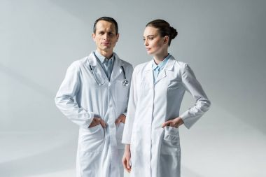 confident adult doctors in white coats on grey