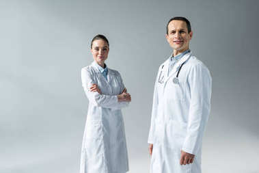 smiling adult doctors looking at camera isolated on grey