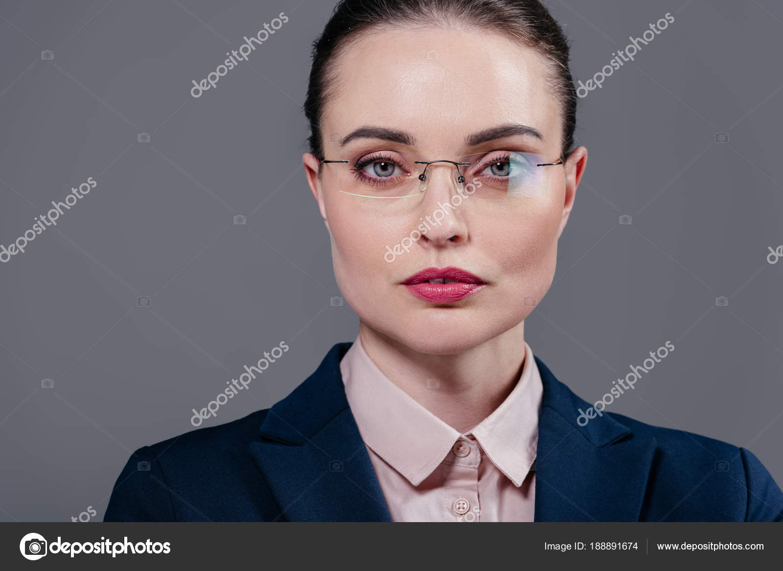 50a5d9c3a0 Beautiful adult businesswoman in stylish eyeglasses looking at camera  isolated on grey– stock image