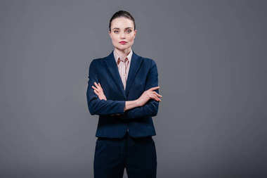 serious adult businesswoman with crossed arms looking at camera isolated on grey