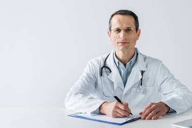 handsome adult doctor sitting at workplace and writing diagnosis in clipboard isolated on white