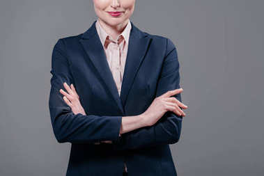 cropped shot of smiling businesswoman with crossed arms isolated on grey