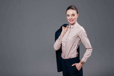 smiling adult businesswoman with jacket on shoulder isolated on grey