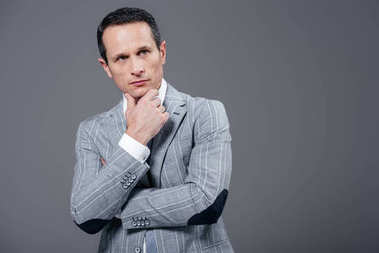 thoughtful adult businessman with hand on chin looking away isolated on grey