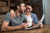 Fotografie Glückliches Paar Frühstück mit Kaffee und Zeitung in der Küche