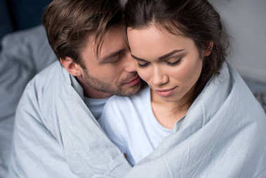 Young man and woman tenderly embracing under blanket