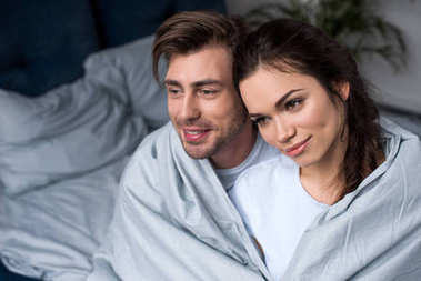 Beautiful couple tenderly embracing under blanket