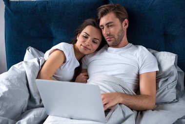 Smiling couple working on laptop while lying in bed