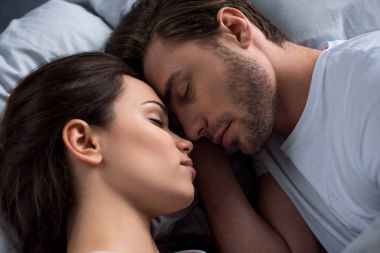 Happy young couple sleeping in bed