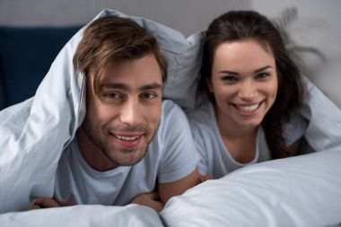 Smiling man and woman lying in bed under blanket