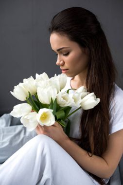 Attractive woman sitting on bed and holding bouquet of tulips