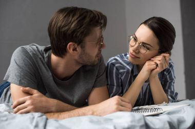 Young couple with notepad lying in bed and looking at each other