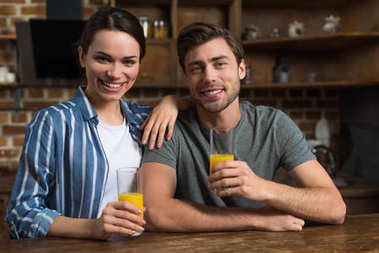 Smiling couple drinking juice by kitchen table