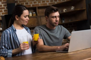 Wife offering juice to her husband working at laptop