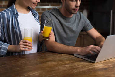 Young woman holding glasses with juice while man working on laptop