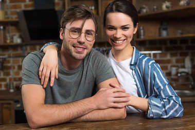 Embracing young couple sitting by table in kitchen