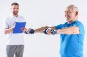 portrét rehabilitačním pracovníkem s Poznámkový blok pomáhat starší muž cvičení s činkami izolované Grey