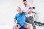 portrait of rehabilitation therapist assisting senior man exercising with dumbbell on grey backdrop