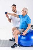 rehabilitační pracovník pomáhat starší muž cvičení s činkami na fitness míče