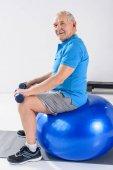 Fotografie boční pohled na starší muž s činkami sedí na fitness míč na šedém pozadí