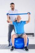 Fotografia terapista della riabilitazione che aiuta uomo senior che si esercita con nastro di gomma sulla sfera di forma fisica