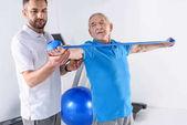 Fotografia Ritratto di terapista della riabilitazione che aiuta uomo senior che si esercita con nastro in gomma
