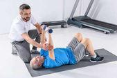 rehabilitační pracovník pomáhat starší muž cvičení s činkami na mat