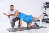 Fotografia terapista della riabilitazione aiutando sorridente uomo senior che si esercita sulla stuoia