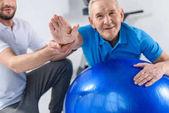Fotografia vista parziale del terapista della riabilitazione assistenza delluomo senior sorridente che si esercita sulla sfera di forma fisica