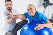 Selektivní fokus rehabilitační pracovník pomáhat starší muž cvičení na fitness míče