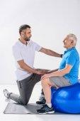 boční pohled na rehabilitační pracovník pomáhat starší muž cvičení na fitness míč na šedém pozadí