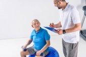 rehabilitační pracovník v poznámkovém bloku pomoc starší muž cvičení s činkami na šedém pozadí