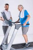 rehabilitační pracovník pomáhat starší muž s ručníky cvičení na běžeckém pásu izolované Grey