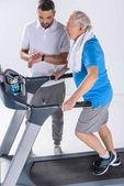 Fotografia terapista della riabilitazione controlla tempo mentre assisteva uomo maggiore che si esercita sulla pedana mobile isolata su grey