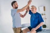 portrét rehabilitační pracovník dělá masáž na starší muž na masážní stůl
