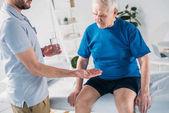 oříznuté záběr rehabilitační terapeut dávat prášek do starší muž na masážní stůl