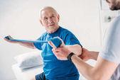 Oříznout záběr rehabilitační pracovník pomáhat starší muž cvičení s gumovou páskou