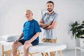 rehabilitační pracovník s stetoskop a starší muž na masážní stůl