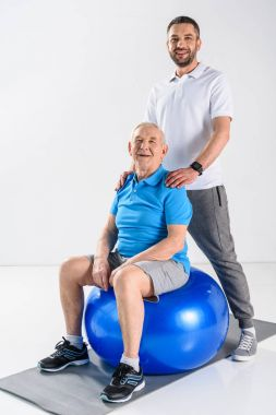 smiling rehabilitation therapist and senior man on fitness ball looking at camera on grey backdrop