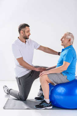 side view of rehabilitation therapist assisting senior man exercising on fitness ball on grey backdrop