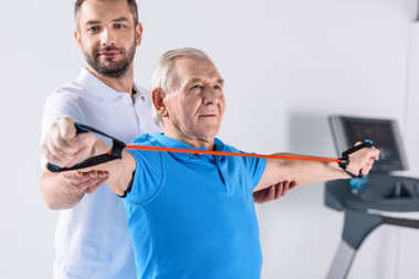 smiling rehabilitation therapist assisting senior man exercising with rubber tape